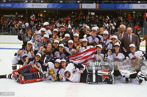 Members of United States women's hockey team and coaching staff pose for a team portrait on the ice following the medal ceremony where they were...