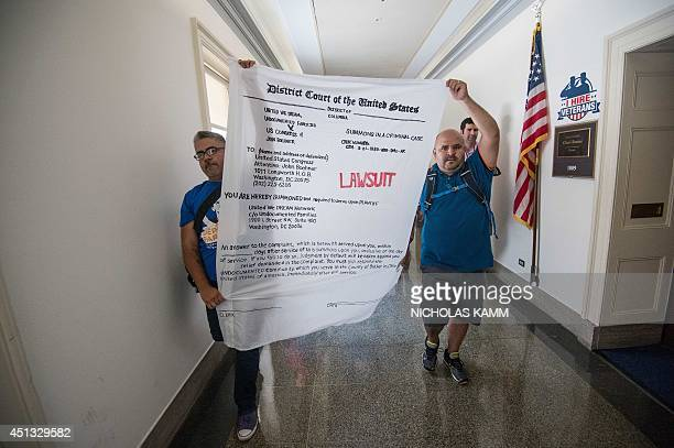 Members of United We Dream carry a banner representing a lawsuit against US House Speaker John Boehner as they walk to his office on Capitol Hill...