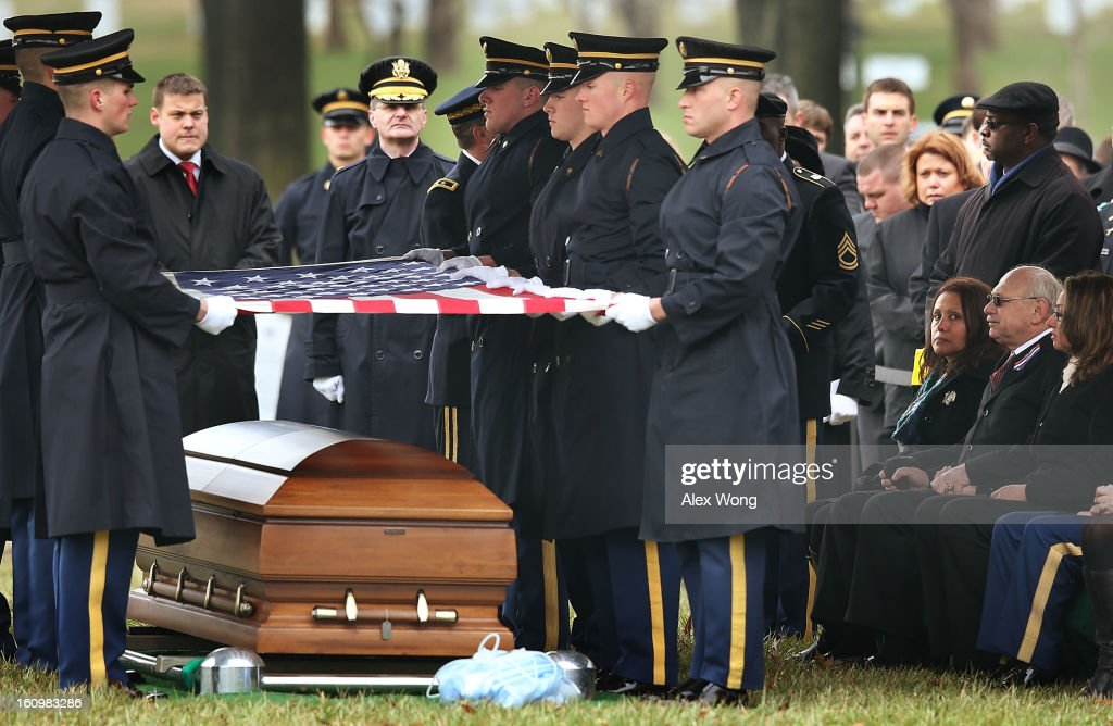 Members of U.S. Army's 3rd Infantry Regiment 'The Old Guard' hold a flag over the casket of Army Sergeant Aaron X. Wittman as Wittman's parents Bertha (3rd R) and Duane (2nd R) look on during his funeral February 8, 2013 at Arlington National Cemetery in Arlington, Virginia. Sergeant Wittman, 28, of Chester, Virginia, was assigned to 3rd Battalion, 69th Armor Regiment, 1st Brigade Combat Team, 3rd Infantry Division in Fort Stewart, Georgia. He died on January 10, 2013 in Khogyani District of Nangarhar Province in Afghanistan, from injuries sustained after his unit was hit by a small arms fire.