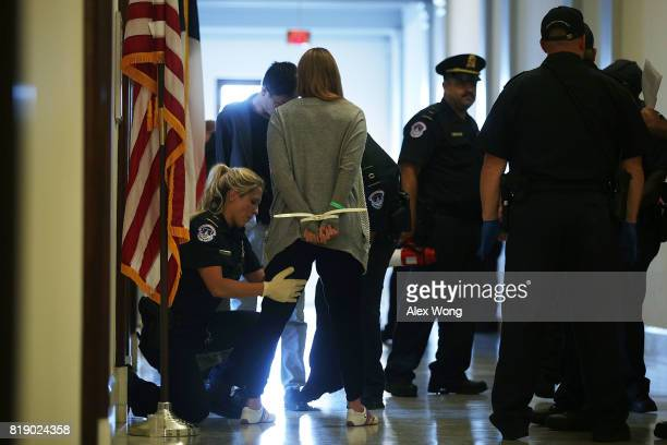 Members of US Capitol police arrest an activist outside US Sen Ted Cruz's office in the Russell Senate Office Building in a protest against the...