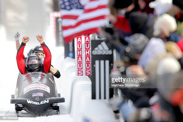 Members of USA 1 piloted by Steven Holcomb celebrate after crossing the finish line to win the four man competition during the FIBT Bobsled World...