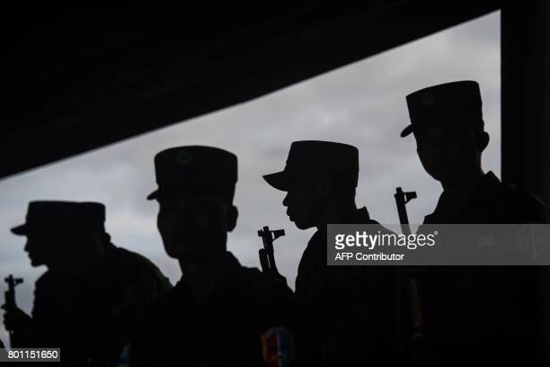 Members of UWSA stand guard during a drug burning ceremony to mark the UN's world antidrugs day in Poung Par Khem near the Thai and Myanmar border on...