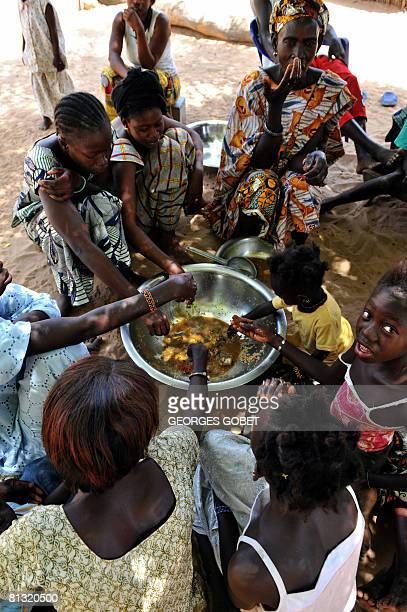 Members of various families eat a dish served during the mid day meal in the village of Merine Dakhar on May 29 2008 A lack of rainfall and...