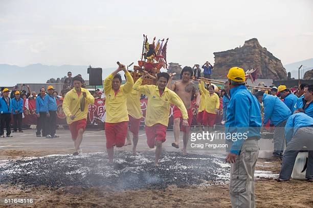 Members of village temples in a fishing village carry God icons across hot coals during the annual harbor cleansing ritual The event takes place on...
