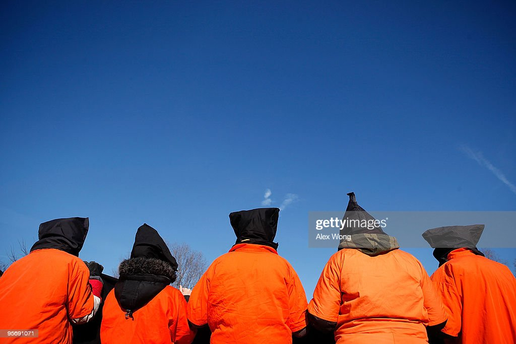 Members of Witness Against Torture wear orange jumpsuits as they protest in front of the White House to mark the eighth anniversary of the opening of Guantanamo Bay detention camp January 11, 2010 in Washington, DC. Protesters called on the Obama Administration to close down the detention facility.