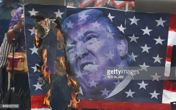 Members of women's group Gabriela burn a mock US flag with a portrait of President Donald Trump during a rally to celebrate International Women's Day...