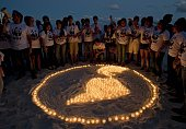 Members of WWF make a representation of the Earth with lit candles in a beach in Cancun on December 5 in the framework of the United Nations...
