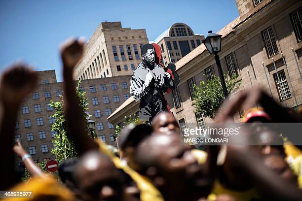 ANC members shout slogan against the South African police under a statue of a boxing Nelson Mandela to disrupt a march by the South African...