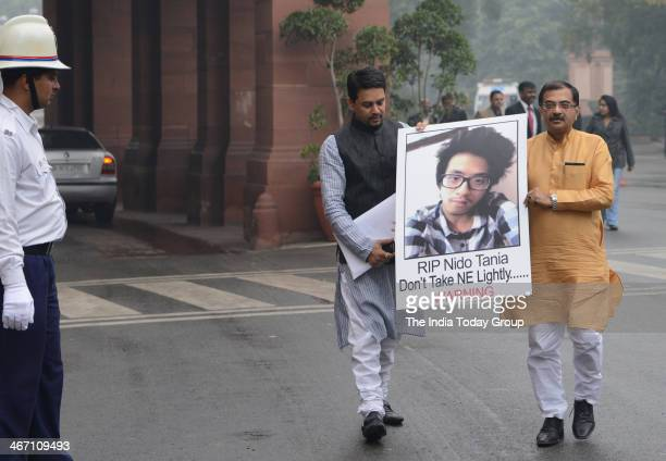BJP members Tarun Vijay and Anurag Thakur holding a poster of Arunachal Pradesh student Nido Tania who was killed recently at Parliament House