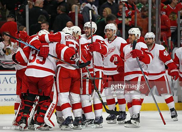 Membes of the Detroit Red Wings mob Jimmy Howard after a shootout win over the Chcago Blackhawks at the United Center on February 18 2015 in Chicago...