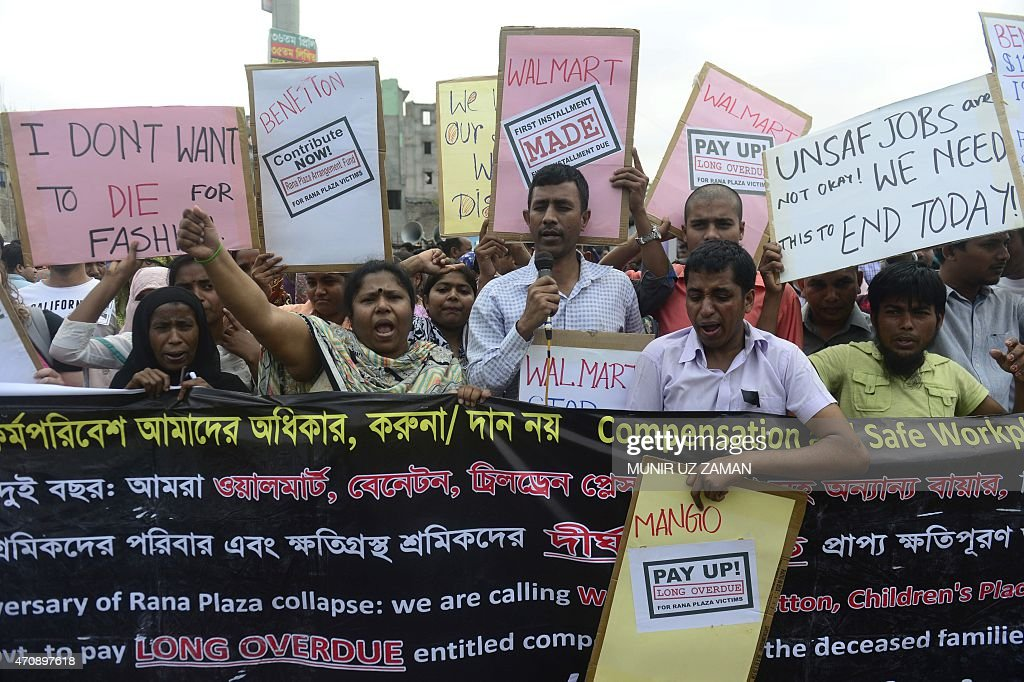 Memebers of Bangladeshi garments worker union shout slogans as they mark the second anniversary of the Rana Plaza building collapse at the site where the building once stood in Savar, on the outskirts of Dhaka on April 24, 2015. Demonstrators, including hundreds of survivors cried for compensation and demanded safety and labour rights in thousands of garment factories as they held demonstrations just outside Dhaka to mark the second anniversary of one of the world' worst industrial disasters, which left at least 1,138 people dead and more than 1,500 people injured. AFP PHOTO / Munir uz ZAMAN