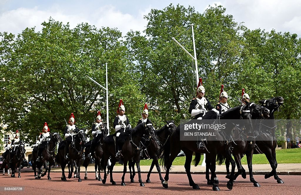 Memebers of the Blues and Royals, one of the squadrons that form the Household Cavalry Mounted Regiment, ride their horses towards Hourse Guards Parade in central London on June 28, 2016. EU leaders attempted to rescue the European project and Prime Minister David Cameron sought to calm fears over Britain's vote to leave the bloc as ratings agencies downgraded the country. Britain has been pitched into uncertainty by the June 23 referendum result, with Cameron announcing his resignation, the economy facing a string of shocks and Scotland making a fresh threat to break away. / AFP / BEN