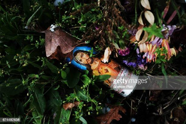 A memorial candle sits in the grass near where the bodies of four brutally beaten young men were recently discovered on April 28 2017 in Central...