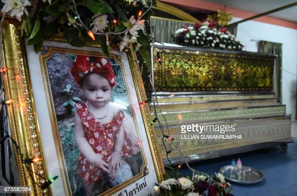 A memorial photograph of slain 11month old girl Natalie is displayed in front of her coffin at a temple in Phuket on April 27 2017 Thai media came...
