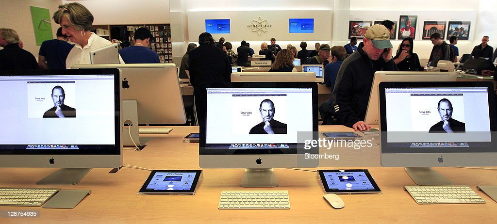 A memorial photograph of Steve Jobs, co-founder and former chief executive officer of Apple Inc., is displayed on iMac computers at an Apple store in Palo Alto, California, U.S., on Friday, Oct. 7, 2011. Jobs, who built the world's most valuable technology company by creating devices that changed how people use electronics and revolutionized the computer, music and mobile-phone industries, died on Oct. 5. He was 56. Photographer: Tony Avelar/Bloomberg via Getty Images