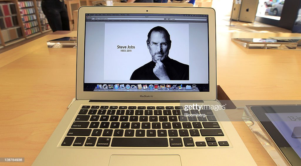 A memorial photograph of Steve Jobs, co-founder and former chief executive officer of Apple Inc., is displayed on a MacBook Air computer at an Apple store in Palo Alto, California, U.S., on Friday, Oct. 7, 2011. Jobs, who built the world's most valuable technology company by creating devices that changed how people use electronics and revolutionized the computer, music and mobile-phone industries, died on Oct. 5. He was 56. Photographer: Tony Avelar/Bloomberg via Getty Images