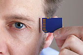 Inserting SD memory card into slot in human head concept for memory upgrage, forgetfulness or computing