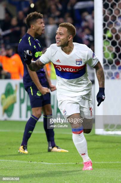 Memphis Depay of Lyon celebrates scoring the third goal while Mason Holgate of Everton reacts during the UEFA Europa League group E match between...