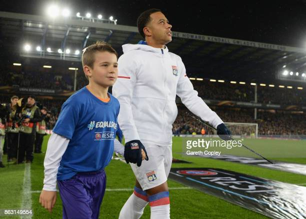 Memphis Depay of Lyon holds the #equalgame banner alongside a mascot prior to the UEFA Europa League Group E match between Everton FC and Olympique...