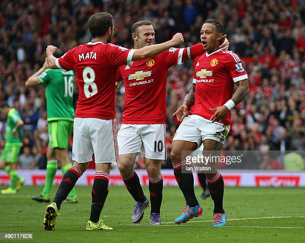 Memphis Depay of Manchester United celebrates scoring his team's first goal with his team mate Juan Mata and Wayne Rooney during the Barclays Premier...