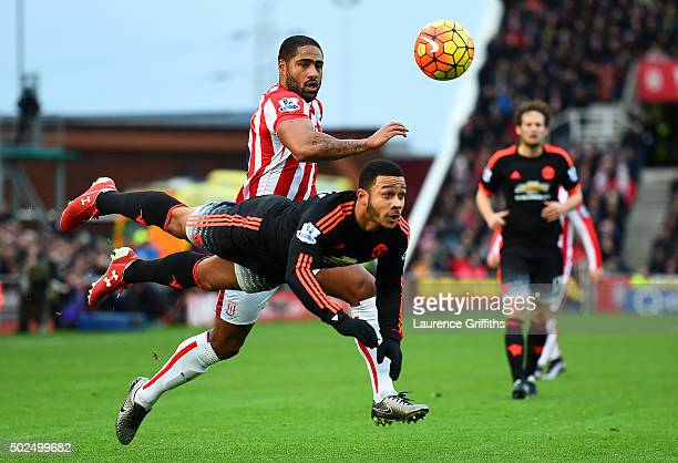 Memphis Depay of Manchester United heads the ball under pressure from Glen Johnson of Stoke City during the Barclays Premier League match between...