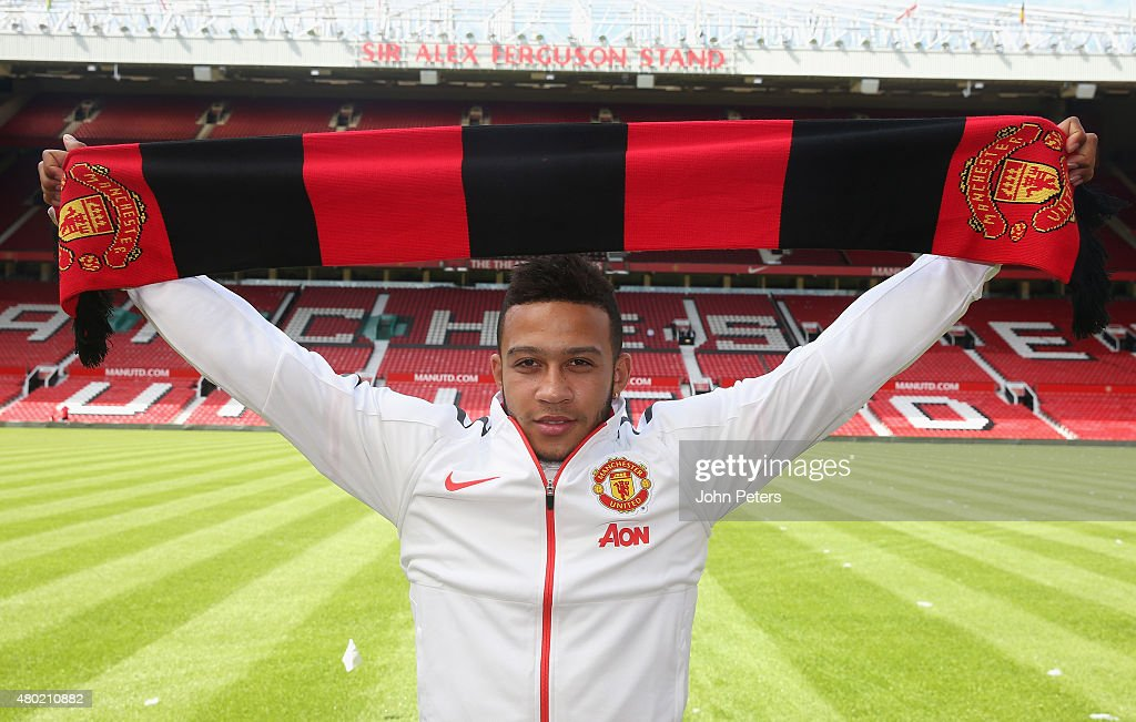 Memphis Depay of Manchester United poses with a club scarf ahead of a press conference to announce his signing at Old Trafford on July 10 2015 in...