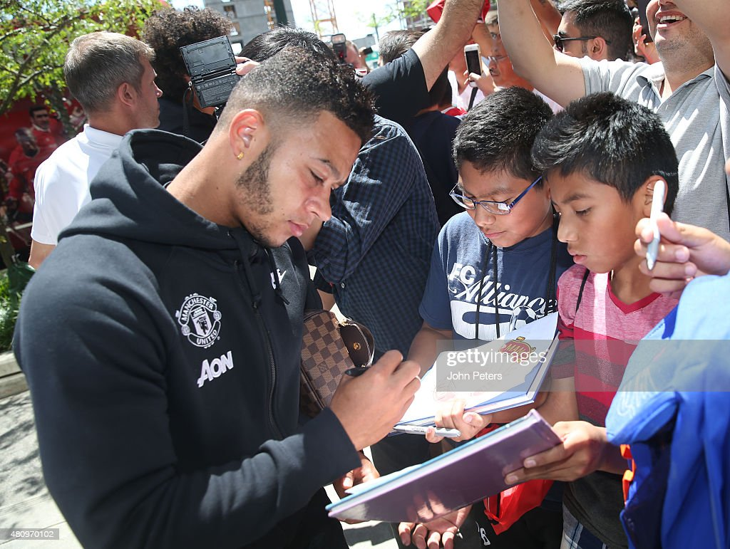Memphis depay of manchester united signs autographs after a training