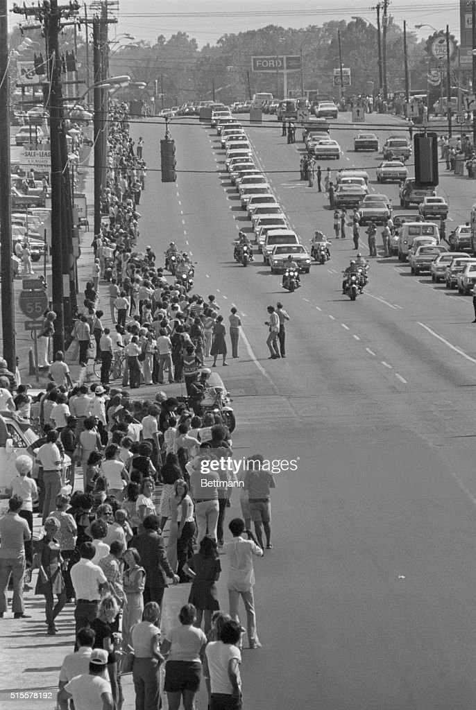 Thousands of people stand on the sidewalk and in the street to watch the funeral procession of Elvis Presley 8/18. 8/18/1977