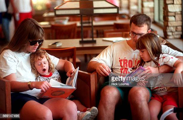 MEmvlibraryread1025RL–Mision Viejo–Nancy LaRue reads to her daughter Amy while her husband Rich reads to their other daughter Allison during the...