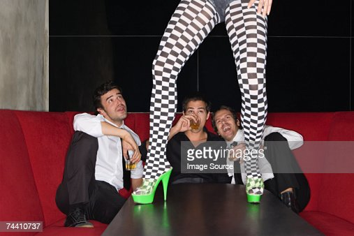 Men and legs of table dancer