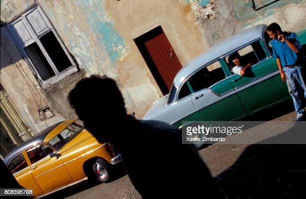Men and vintage cars in a street on November 24 2002 at Santiago de Cuba Cuba