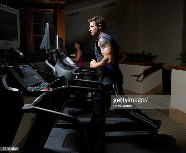 Men and woman exercising on treadmill in gym, side view