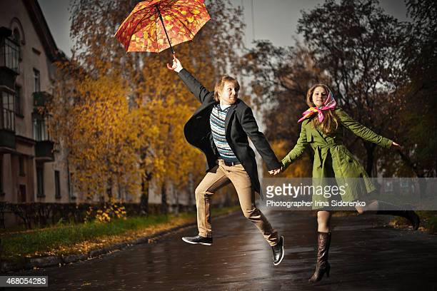 Men and woman jumping with umbrella