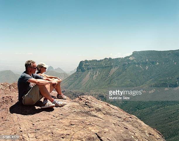 Men and woman sitting on moutain top