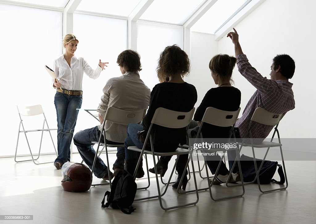 Men and women attending seminar, man raising hand