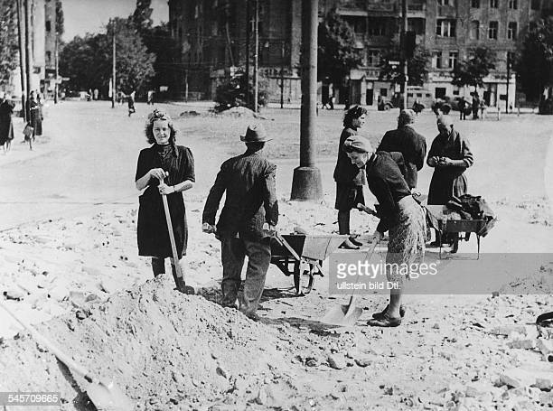 Men and women clean up rubble and debris in the Western city centre of Berlin in August 1945