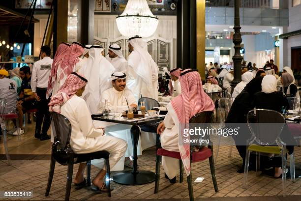 Men and women consume food and drink at a cafe terrace in Avenues shopping mall in Kuwait City Kuwait on Sunday Aug 13 2017 Kuwait will issue a...