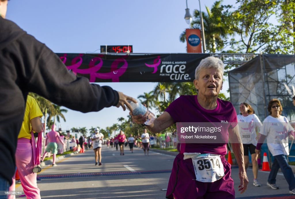 Men and women cross the finish line of a 5 kms charity run to support breast cancer research in the 22nd annual Susan G. Komen Race for the Cure January 26, 2013 in West Palm Beach, Florida. Approximately 15,000 people took part in the charity run. Since 1982, nearly $2 billion has been raised for breast cancer research by the organization.
