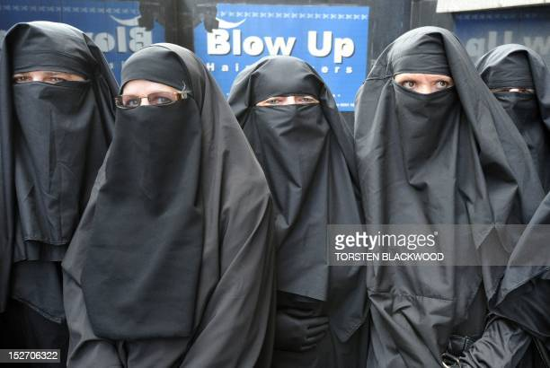 Men and women dressed in burqas from the group 'Faceless' call for the banning of the conservative Muslim apparel throughout Australia during a rally...
