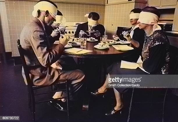 Men and women in a blindfolded focus group participate in a taste test of meats in a mock kitchen at the Department of Agriculture Beltsville...