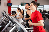 Profile view of a couple of men and a woman doing some cardio on a treadmill in a gym
