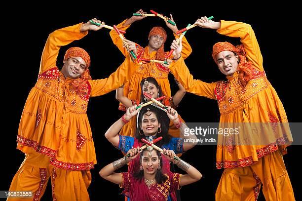 Men and women performing dandiya