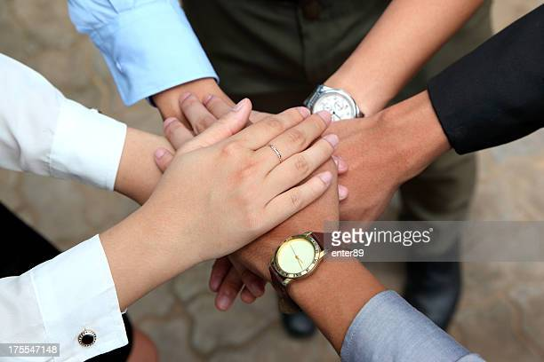 Men and women showing unity by putting their hands together