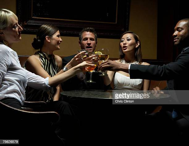 Men and women sitting round table toasting glasses