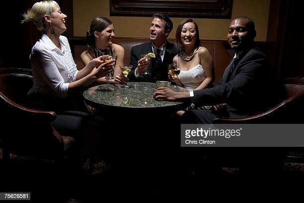 Men and women sitting round table with drinks, upper half