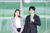 It is Men and women standing in front of the automatic door (business double-income, husband and wife, co-worker)