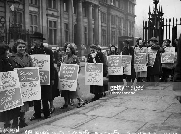 Men and women take part in a protest march demanding equal pay for female employees of the British civil service