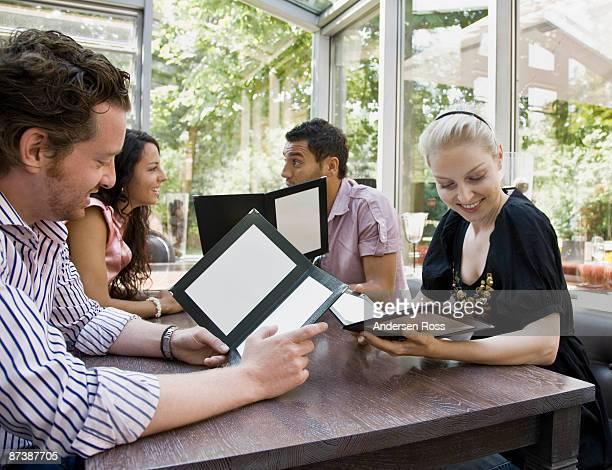 Men and women talking over menus