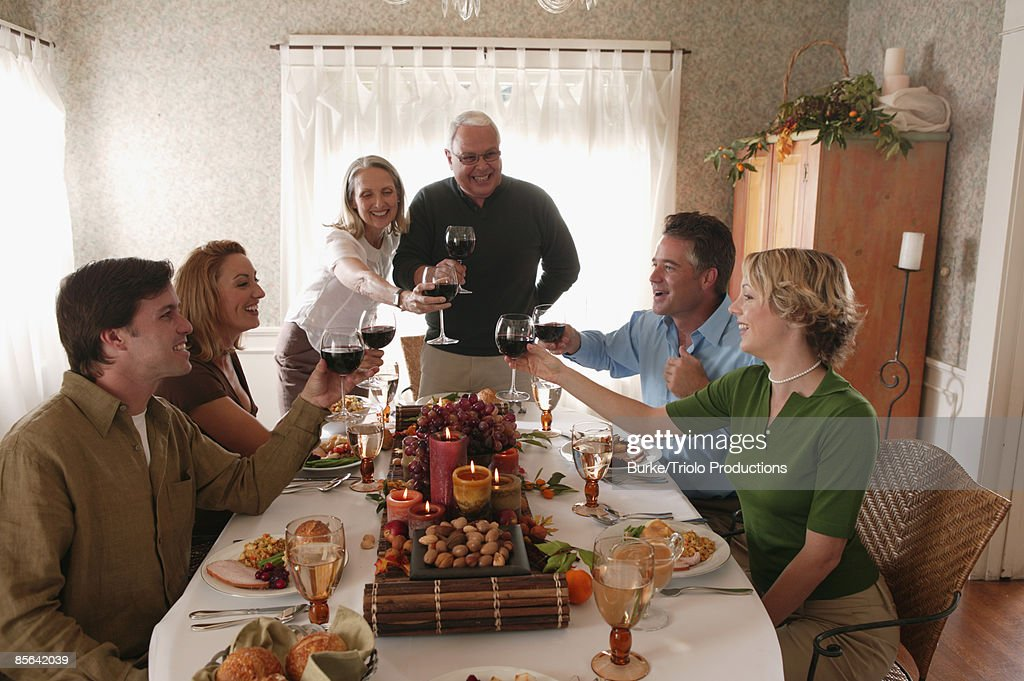 Men and women toasting at holiday feast : Stock Photo
