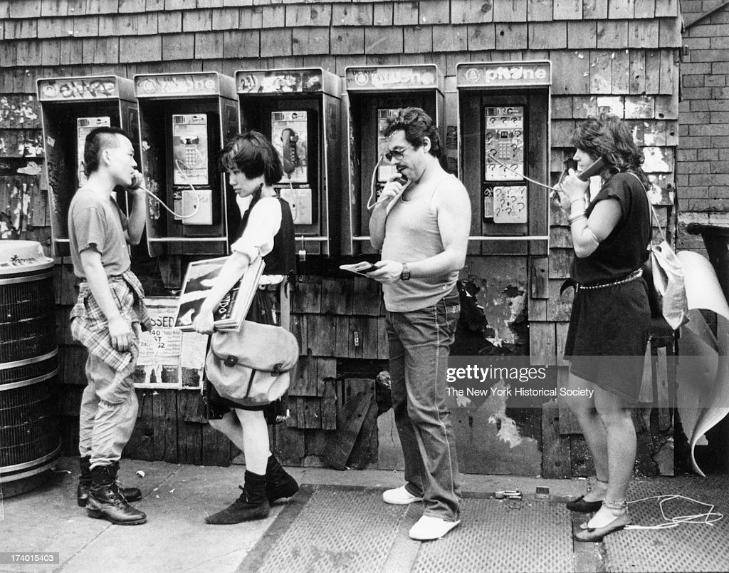 Men and women use public pay phones in the East Village, New York, New York, 1985.